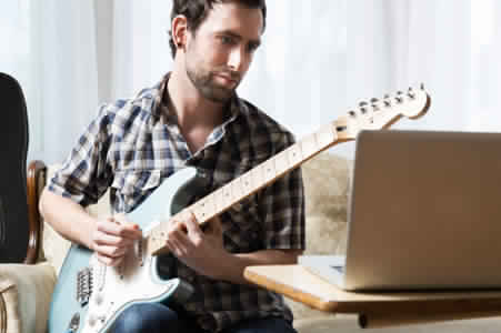 man-with-laptop-and-guitar